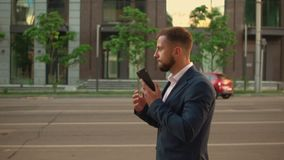 Handsome white collar worker walk use mobile. Successful young businessman walking along the road has phone negotiation city view. candid man using smartphone stock video
