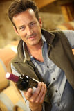Handsome winegrower in wine cellar. Handsome winegrower holding bottle of red wine Stock Photo