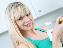Handsome woman eat yogurt in a kitchen Royalty Free Stock Image