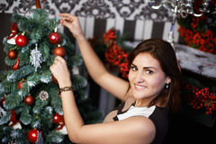 Handsome woman near the holiday Christmas tree Royalty Free Stock Image
