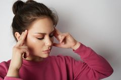 Handsome woman in pink hoody with a severe headache with the hands in the head over white empty wall on background. Beauty and healthcare concept royalty free stock photography