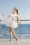 A handsome woman is posing on a hotel`s balcony. The glamorous lady in a fluffy short white dress near the sea beach. stock images