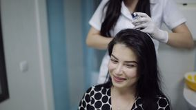 Handsome woman receiving an injection in the head. mesotherapy. Thrust to strengthen the hair and their growth stock video