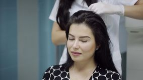 A beautiful young woman receives an injection in the head in the center of aesthetic medicine. Prevention and treatment stock footage