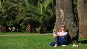 Handsome woman sitting under a palm tree and browsing the Internet on a smartphone.  stock video