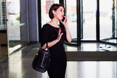 Handsome woman walking and talking on mobile phone. Stylish and handsome woman walking and talking on mobile phone in shopping center Royalty Free Stock Image