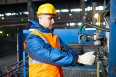 Handsome Worker Adjusting Equipment. Profile view of confident bearded worker wearing hardhat and reflective vest standing at spacious production department of Royalty Free Stock Image