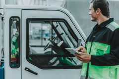 Handsome worker looking at the transport on the workplace stock photography