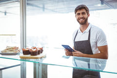 Handsome worker posing on the counter with a tablet. At the bakery Stock Photos