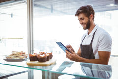 Handsome worker posing on the counter with a tablet Royalty Free Stock Image