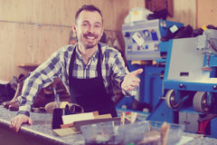 Handsome worker showing his workplace and tools. Handsome male worker showing his workplace and tools in shoe repair workshop Royalty Free Stock Photo