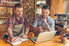 Handsome workers at cafe. Two handsome young cafe workers are using a laptop, making notes, talking and smiling while standing at the bar counter Royalty Free Stock Photography