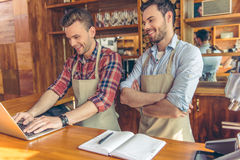 Handsome workers at cafe. Two handsome young cafe workers are using a laptop, talking and smiling while standing at the bar counter Royalty Free Stock Image