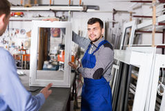 Handsome workers with different PVC windows. Handsome production workers in coverall with different PVC windows and doors royalty free stock images