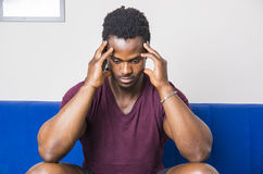 Handsome worried black man sitting on couch. Handsome worried, bothered, sad, muscular black man sitting on couch at home, looking at camera Royalty Free Stock Photo