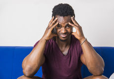 Handsome worried black man sitting on couch. Handsome worried, bothered, sad, muscular black man sitting on couch at home, looking at camera Stock Images