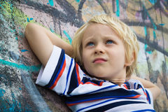 Handsome worried boy thinking against graffiti wall Royalty Free Stock Photography