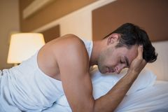 Handsome worried man having a headache lying on the white bed. B. Edroom background Stock Image