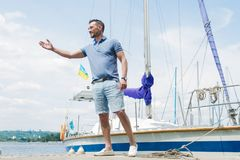 Handsome yachtsman walking at river pier and welcomes visitors. Young businessman invites to his boat for yacht adventure. stock image