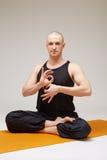 Handsome yogi posing at camera while meditating Royalty Free Stock Image