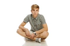 Handsome youn man sitting on the floor Royalty Free Stock Photos