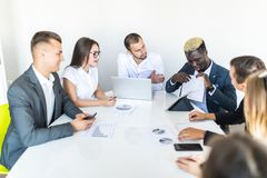 Handsome young african american businessman presenting figures at a meeting with team. Team work stock image