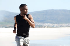 Handsome young african american man running on the beach Royalty Free Stock Images