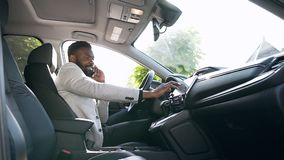 Handsome young african american man sitting on the front leather seat black luxury car and tunes the vehicle touch. Screen while speaking on his mobile. Slow stock video