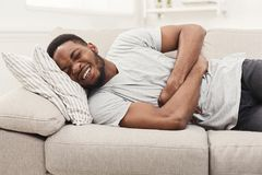 Handsome young african-american man suffering from stomachache. Handsome young african-american man suffering from stomach ache while lying on sofa at home Stock Photography