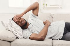 Handsome young african-american man suffering from stomachache and headache. While lying on sofa at home royalty free stock image