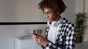 Handsome young African American man using his mobile phone while sitting on table at home. Video of handsome young African American man using his mobile phone stock video