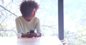 Black woman drinking coffee and using a mobile phone  at home. Handsome young african american woman drinking coffee and using a mobile phone at  home Royalty Free Stock Images