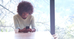 Black woman drinking coffee and using a mobile phone at home stock photo