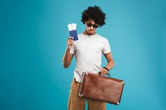 Handsome young african curly man tourist. Photo of handsome young african curly man tourist isolated over blue wall background holding tickets with passport and Stock Images