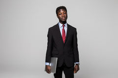 Handsome young African man in formalwear move with laptop in hands while standing against grey background Stock Images