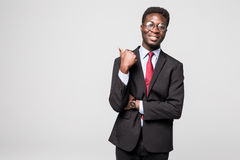 Handsome young African man in formalwear pointing away and smiling while standing against grey background. Successful choice. Handsome young African man in Royalty Free Stock Images