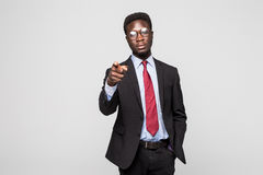 Handsome young African man in formalwear pointing on you while standing against grey background Stock Image