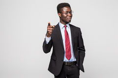 Handsome young African man in formalwear pointing on you while standing against grey background Stock Photo