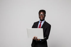 Handsome young African man in formalwear working on laptop while standing against grey background Royalty Free Stock Photos