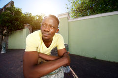 Handsome young african man leaning over iron post on sidewalk Stock Photography