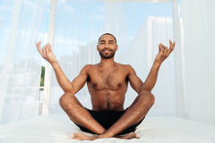 Handsome young african man in shorts sitting and meditating Royalty Free Stock Photography
