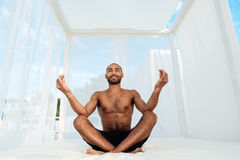 Handsome young african man in shorts sitting and meditating Royalty Free Stock Images