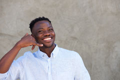 Handsome young african man showing a call me sign and smiling Stock Images
