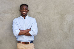 Handsome young african man smiling with arms crossed by wall Stock Image