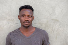 Handsome young african man standing against a wall Stock Photos