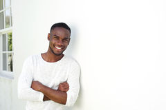 Handsome young african man standing with his arms crossed Stock Photos
