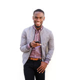 Handsome young african man standing with a mobile phone. Portrait of a handsome young african man standing with a mobile phone against white background Royalty Free Stock Photo