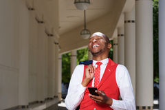 Handsome young african man in suit laughing outdoors with cellphone Stock Image