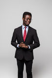 Handsome young African man in suit while standing against grey background Stock Photos