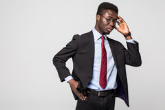 Handsome young African man touching head with hand and looking uncertain while standing against grey background Stock Photos